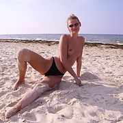 Topless wife at the beach rolling around in the sand