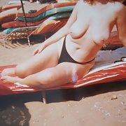 Sexy milf on the beach sunbathing topless