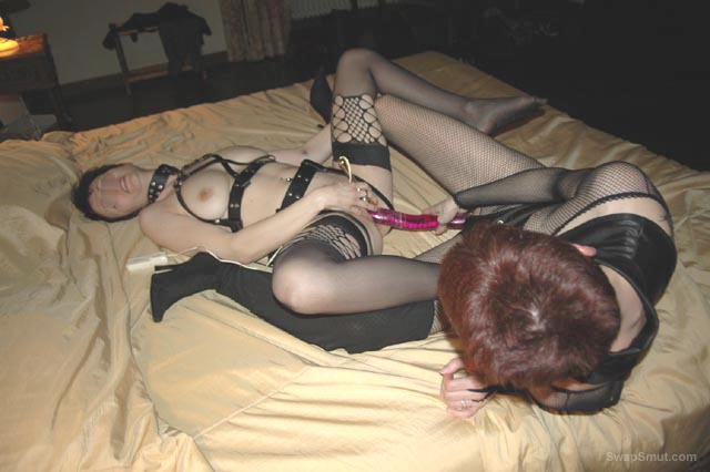 Lesbians at play wearing leather bondage gear double dildo fun