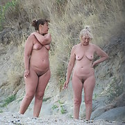 Two beautiful mature woman on the beach hunting for some shells