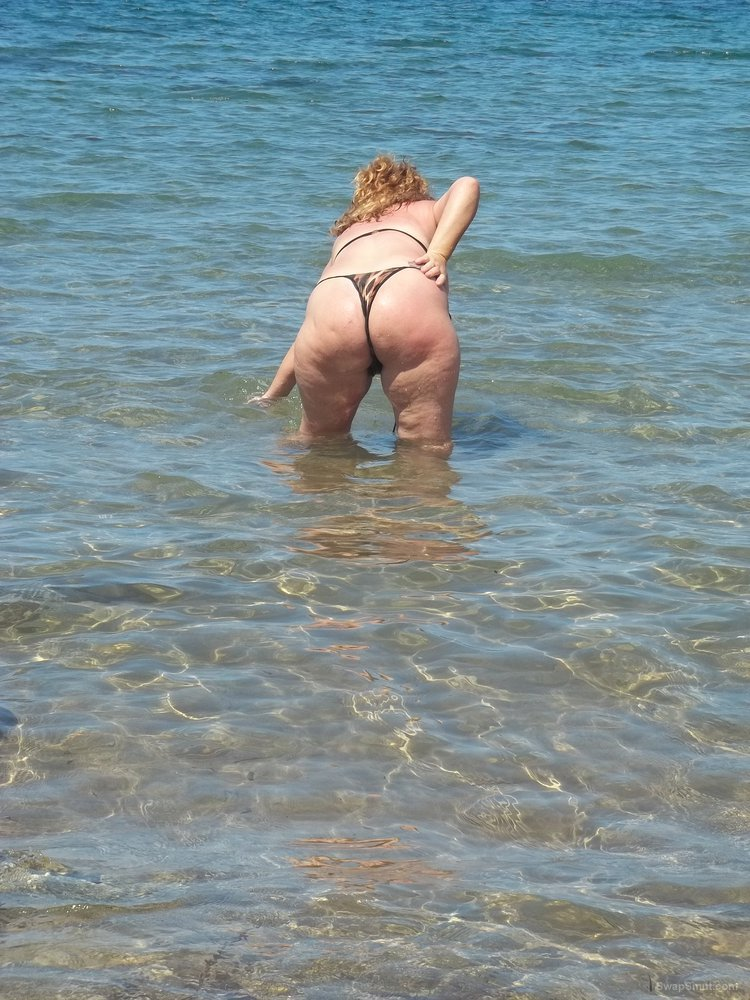 Sexy wife in bikini having photos taken on a beach by the sea