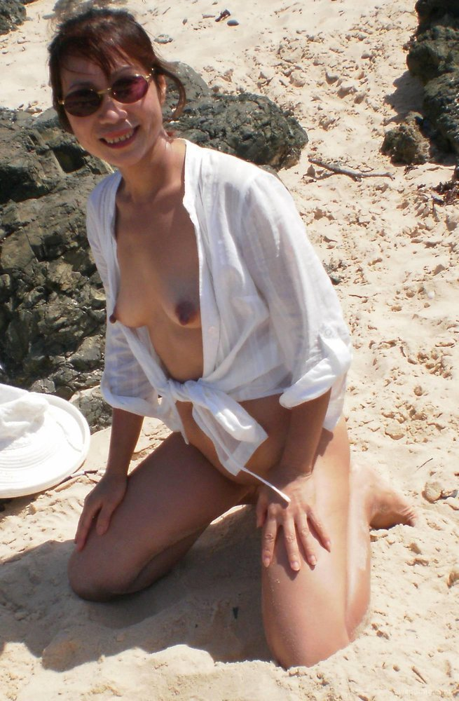 Sexy Asian MILF on Beach feeling sand on smooth skin