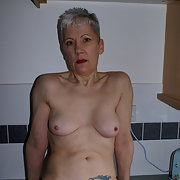 GILF playtime in the kitchen having fun inserting a wooden spoon