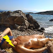 My wife naked sunbathing by the sea