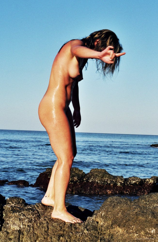 Sexy young gal on the nude beach walking on the rocks