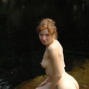 Beautiful athletic redhead stripping off outdoors