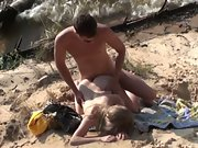 Naked couple has sex on the beach while waves lap at their feet