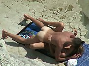 Horny couple sunbathing on a beach get excited and cannot resist sex
