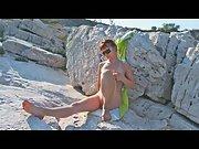 Mother sunning herself naked on rocks overlooking sea on vacation