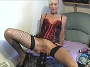 Mature blonde squeezing huge toys inside her