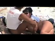 Butt naked wife gives her strong hubby a nice blowjob at the local beach